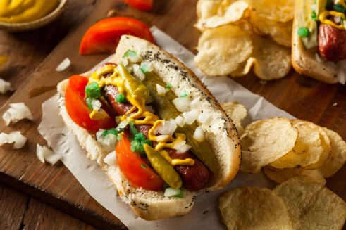 chicago style hot dog with neon relish, onions, tomato wedges, dill pickle spear, yellow mustard, sport peppers, celery salt and poppyseed bun