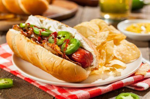 seattle style hot dog with cream cheese, jalapeños, grilled onions and sriracha