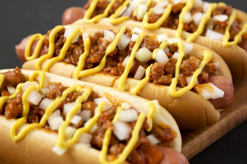 detroit style hot dog with beef chili, raw onions and mustard